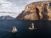Two Old Vintage Sailing Vessels And Icebergs Floating In The Arctic Close To Greenland