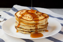 Homemade Pancakes With Butter And Maple Syrup On A White Plate, Side View. Close-up.