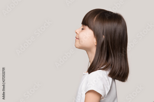 Fotografia  Profile of serene little girl isolated on grey studio background