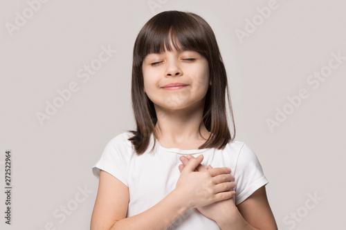 Obraz Little girl closed eyes hold hand on chest feels gratitude - fototapety do salonu