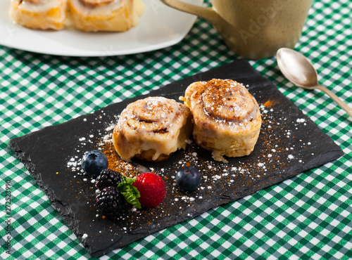 Tasty cinnamon rolls with fresh berries and powdered sugar at plate