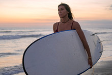 Sporty Girl With A Beautiful Figure Stands With A Surfboard On The Background Of A Sunset By The Ocean