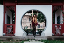 Stylish Young Female Posing By Round Doorway In The Street
