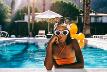 Portrait Of Young Woman With Sunglasses Posing In Swimming Pool
