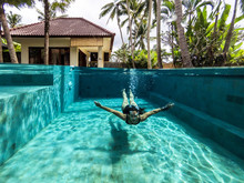 Woman Swimming On The Pool Of A Private Villa In Bali