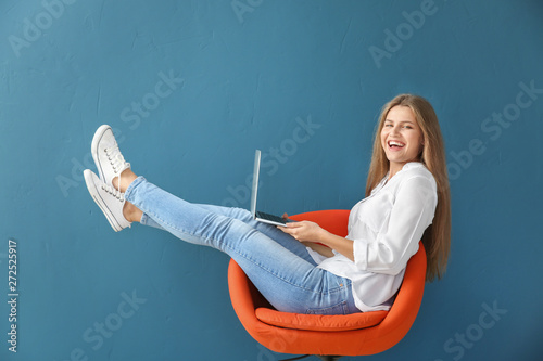 Beautiful young woman with laptop sitting on chair against color background Fototapeta