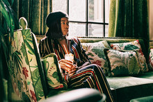 Young Stylish Black Woman Sitting In Green Sofa With Cocktail In