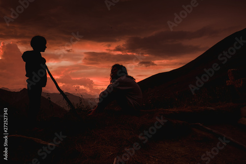 teen and little brother holding stick  in a dramatic sunset in the Alps in France