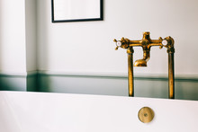 Closeup Of Brass Bathroom Fittings In Beautiful White Bathroom