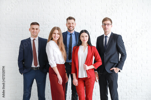 Team of business people near white brick wall