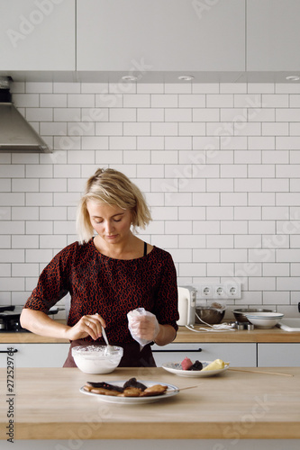 Woman filling pastry bag with icing for cookies