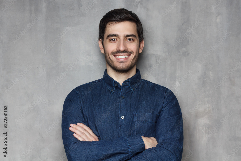 Fototapeta Headshot of Caucasian guy standing with crossed arms and confident look against grey background