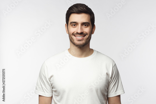 Pinturas sobre lienzo  Portrait of smiling young man in white t-shirt looking at camera, isolated on gr