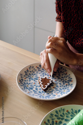 Woman icing cookie in shape of fir tree