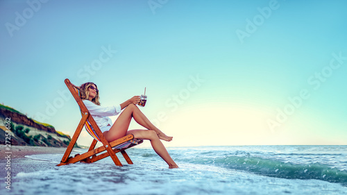 Obraz Pretty woman relaxing on a lounger beach and drinks soda water. summer vacation concept. - fototapety do salonu