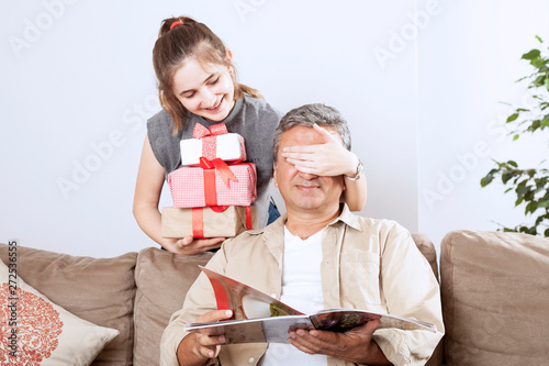 beautiful girl giving a gift box to her father