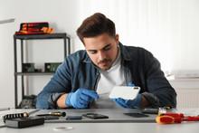 Technician Repairing Broken Smartphone At Table In Workshop