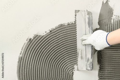 Obraz Closeup of worker spreading concrete on wall with spatula, space for text. Tile installation - fototapety do salonu