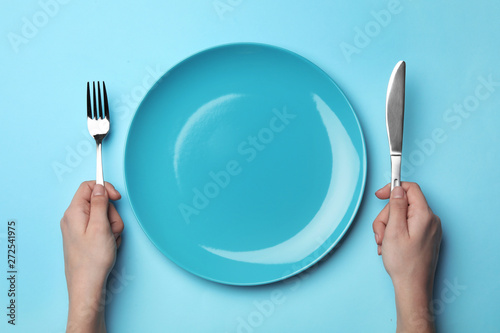 Obraz na płótnie Woman with fork, knife and empty plate on color background, top view