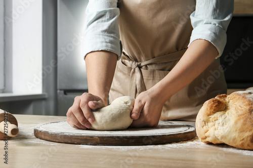 Fototapeta Female baker preparing bread dough at table, closeup