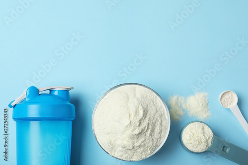 Flat lay composition with protein powder on color background. Space for text