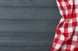 Checkered picnic blanket on color wooden background, top view. Space for text