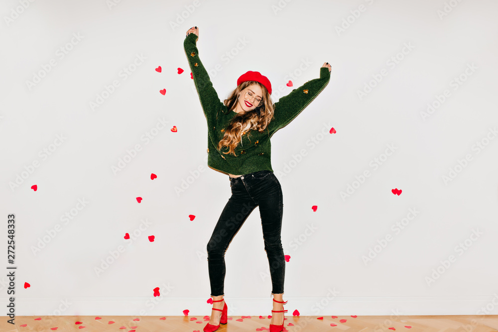 Fototapety, obrazy: Blissful girl in red high heel shoes dancing on white background under heart confetti. Spectacular young woman in french beret having fun in valentine's day.