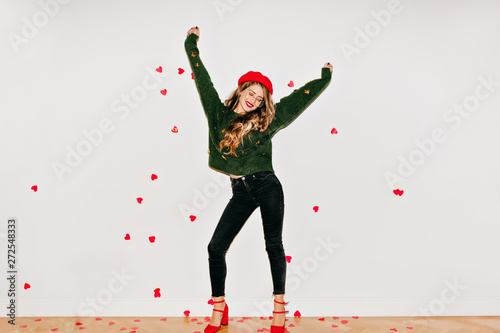 Blissful girl in red high heel shoes dancing on white background under heart confetti. Spectacular young woman in french beret having fun in valentine's day.
