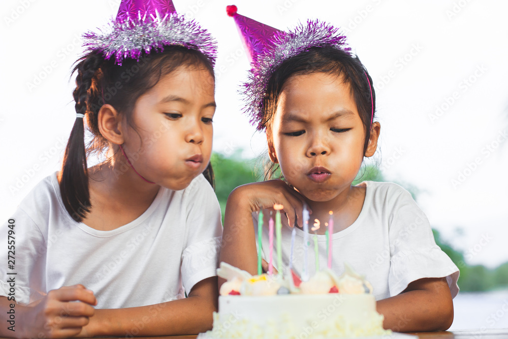 Fototapety, obrazy: Two asian child girls celebrating birthday and blowing candles on birthday cake in the party
