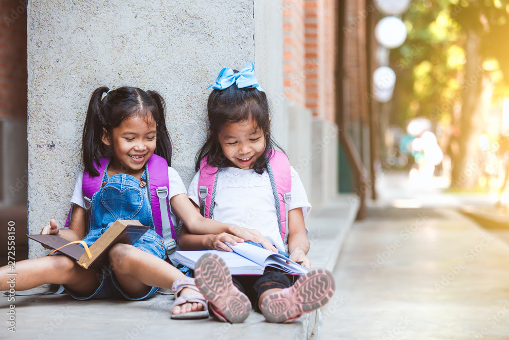 Fototapety, obrazy: Back to school. Two cute asian pupil girls reading a book  together in the school with fun and happiness