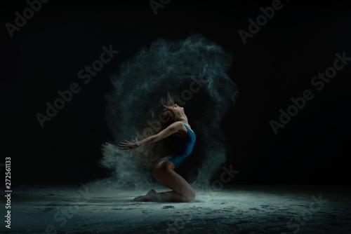 Obraz Graceful barefoot woman dancing in cloud of dust - fototapety do salonu