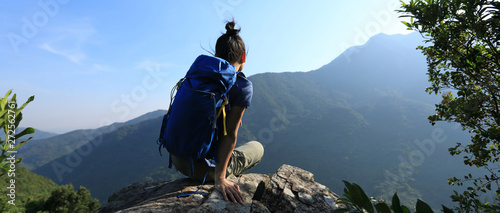 Successful woman backpacker sit on cliff's edge at mountain top