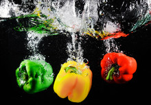 Fresh Green, Yellow And Red Bell Peppers With Water Splash And Bubble Isolated. Colorful Copy Space. Three Colored Paprika Dropping To The Water On Black Background