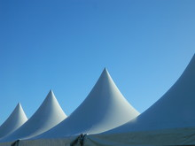 The Tops Of Three Marquee Tents On A Blue Sky Background