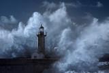 Big wave over old lighthouse
