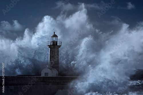 Big wave over old lighthouse