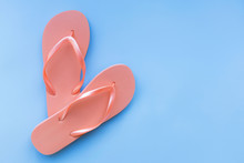 Living Coral Flip Flops On A Blue Background. Color Of The Year 2019. Living Coral. Place For Text.