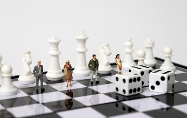 Miniature people standing and chess pieces on the chessboard.