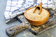Bowl With Sesame Seeds And Wooden Scoop.