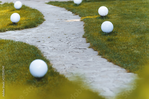 Stoned path in a garden or park covered with grass. Small round garden lamps beside the path.