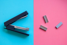 Funny Stapler And Paper Clips On Blue And Pink Vivid Background