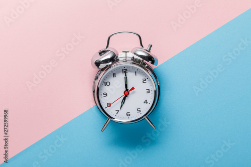 top view of classic silver alarm clock on pink and blue background Canvas Print