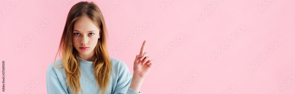 Fototapeta panoramic shot of sad teenage girl pointing with finger isolated on pink