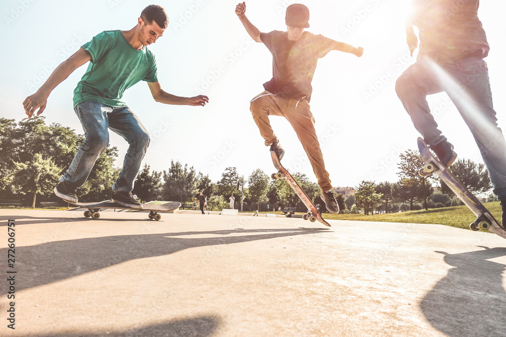 Fototapety, obrazy: Skaters jumping with skateboard in city skate park - Young guys performing tricks and skills at sunset in suburb contest - Extreme sport and youth lifestyle concept - Main focus on left guys feet