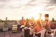 canvas print picture Young friends having barbecue party at sunset on penthouse patio - Happy people doing bbq dinner outdoor cooking meat and drinking wine - Focus on left woman face - Food, fun and friendship concept