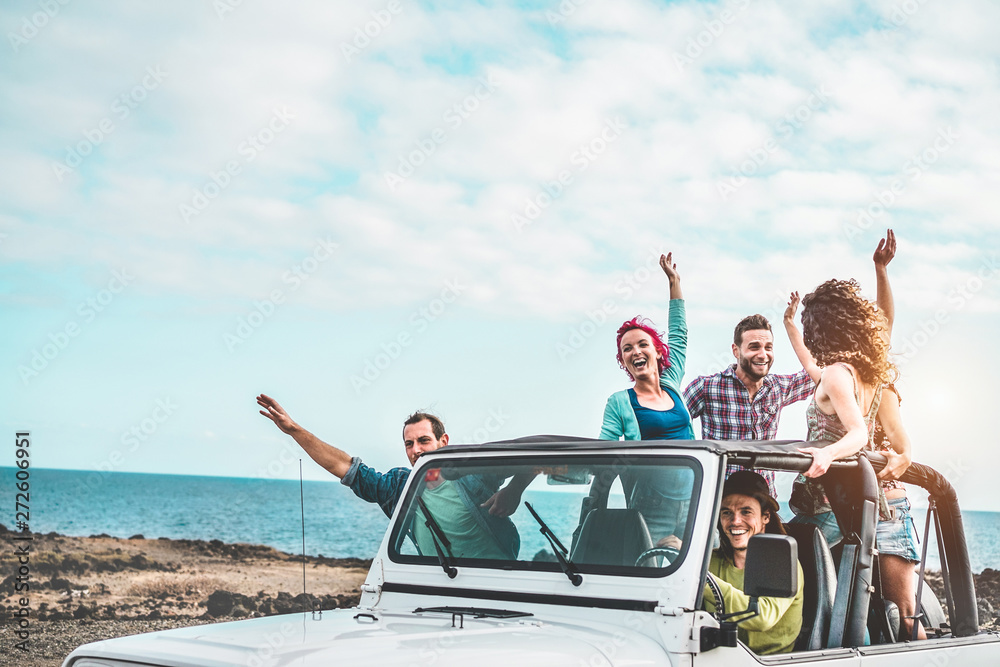 Fototapeta Group of happy friends doing excursion on desert in convertible 4x4 car - Young people having fun traveling together - Friendship, tour, youth lifestyle and vacation concept - Focus on right guys