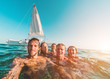 Leinwanddruck Bild Happy friends taking a selfie with action cam inside the ocean with sail boat in background - Young people having fun swimming in the sea - Focus on left man face - Travel and youth concept