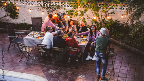 Photo Happy family eating and cheering with red wine at barbecue party dinner - Differ