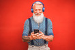 Leinwanddruck Bild - Trendy senior man using smartphone app with red backgorund - Mature fashion male having fun with new trends technology - Tech and joyful elderly lifestyle concept - Focus on his face