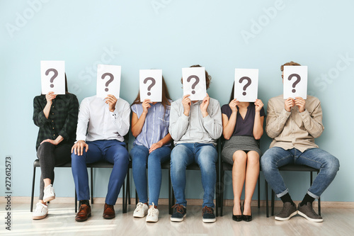 Photo  Young people hiding faces behind paper sheets with question marks while waiting